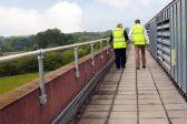 Two gentlemen walking near a silver guardrail