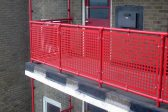 Red guardrails with infill panels on a balcony