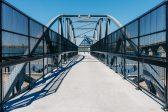 Black guardrails with infill panels on a pedestrian bridge